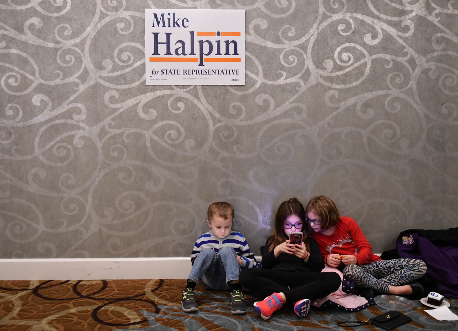 Kaysen Stokes, 4, Kenlie Stokes, 7 and  Kylar Elliott, 7, pass the time by playing games on their devices during the Rock Island County Democrats' election night party, at the Holiday Inn Rock Island, Tuesday Nov. 5, 2018.  (Todd Mizener - Dispatch/Argus)