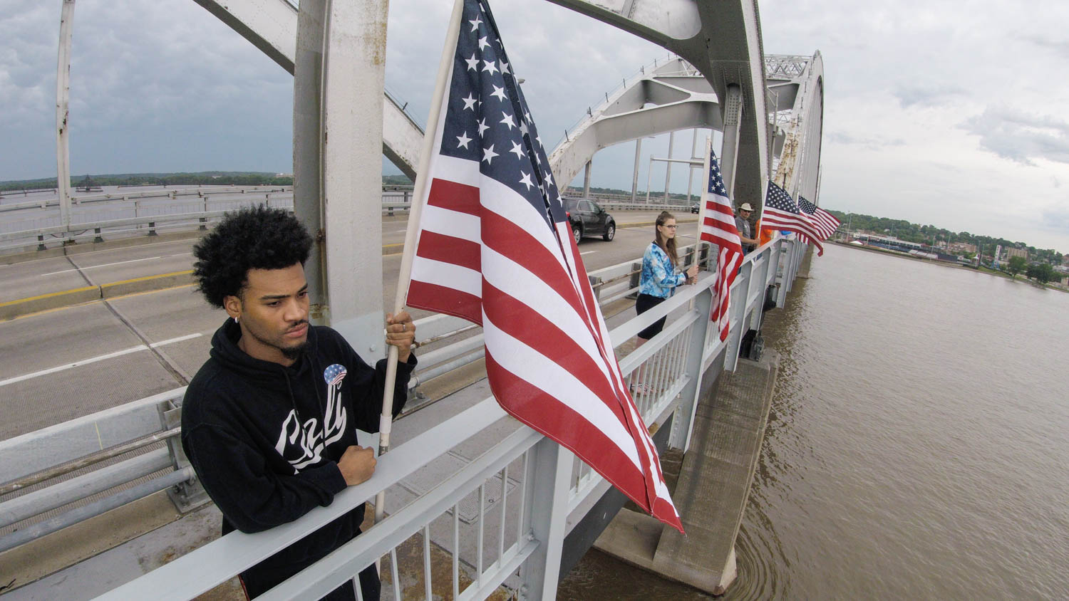 Darron Austin, of Rock Island, and approximately 200 other volunteers line the length of the Master Sgt. Stanley Talbot Memorial Bridge over the Mississippi River between Rock Island and Davenport with U.S. Flags in honor of Flag Day Thursday, June 14, 2018. (Todd Mizener - Dispatch/Argus)