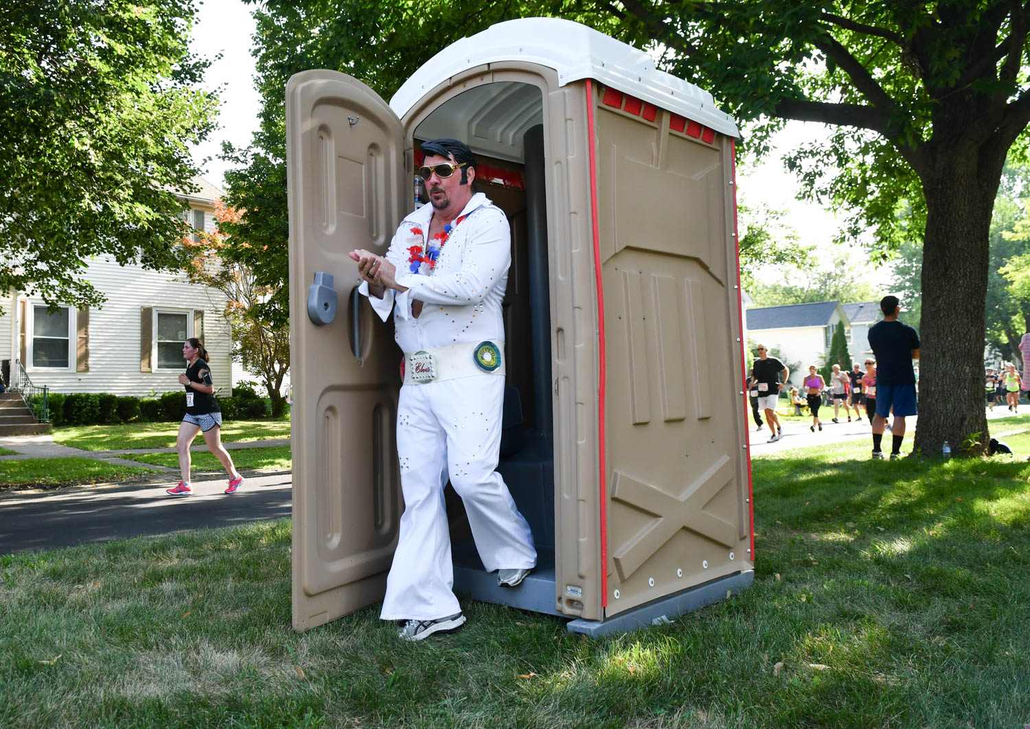 "Running Elvis Scott Cullen, of Taylor Ridge, survives the port-a-potty along Kirkwood Blvd. during the Quad-City Times Bix 7 Saturday, July 28, 2018 in Davenport, Iowa. Upon exiting the port-a-potty Cullen quipped ""Wow. I smells like something died in there."" (Todd Mizener - Dispatch/Argus)"