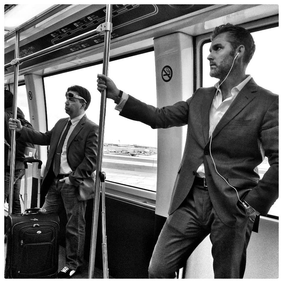 Two travellers exhibit contrasting levels of style while riding the airport shuttle train at Dallas-Fort Worth Airport, Tuesday April 14, 2015. (Photo by Todd Mizener)