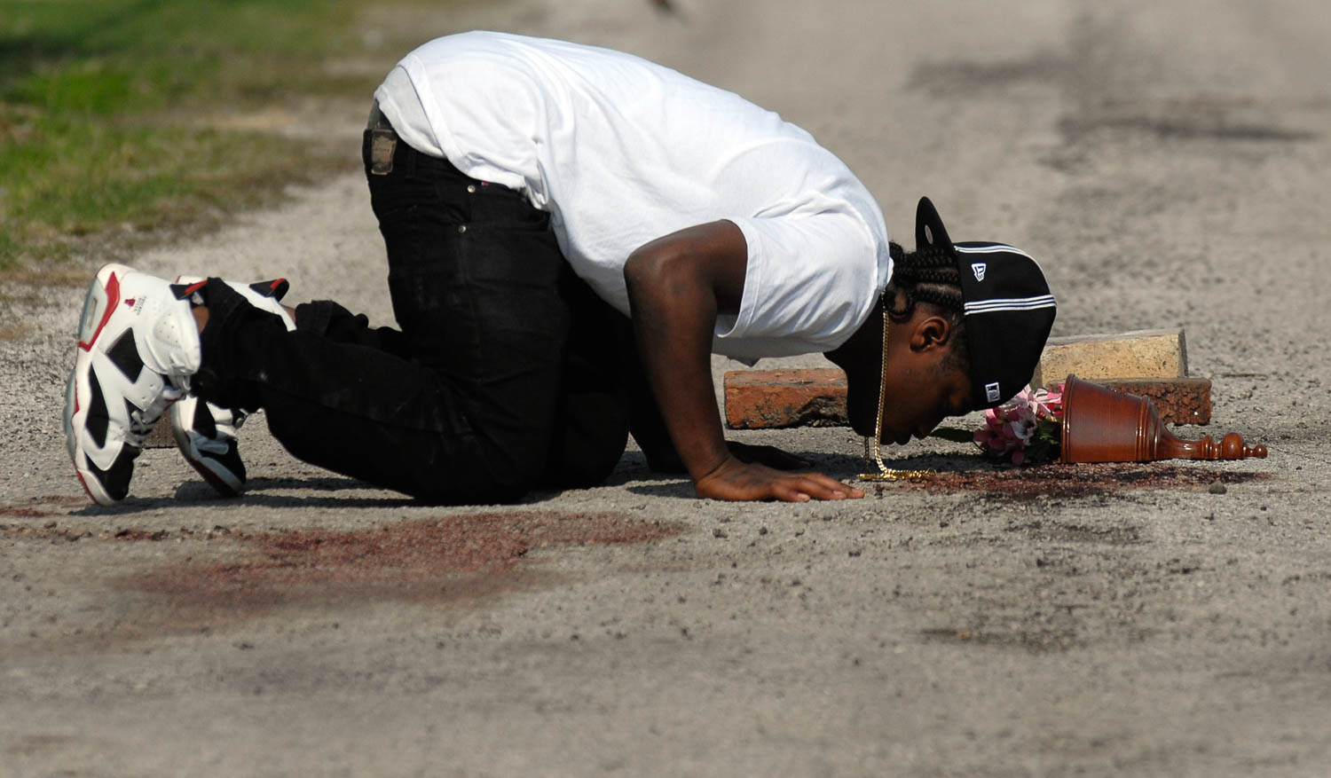 Joe Williams of Carbon Cliff kisses the blood-stained pavement Thursday morning in the East Moline Ill. alley where his cousin Kelton Trice was shot and killed by police Wednesday evening. Police investigators said Trice was killed during an exchange of gunfire with East Moline police officer Sgt. Tom Peterson. (Todd Mizener - Dispatch/Argus)