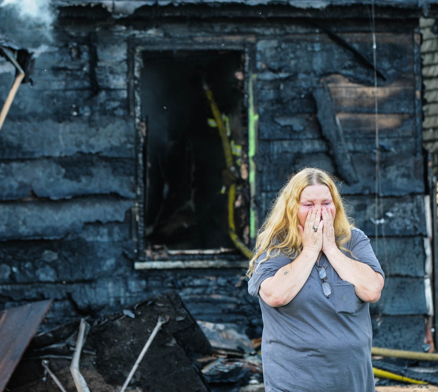 Barb Lucia, of East Moline, reacts to the early-morning fire which destroyed the house she was living in at 1339 17th St., East Moline. Ms. Lucia was not at home when the fire broke out about 6:30 this morning. The three people asleep inside the home escaped uninjured. (Todd Mizener - Dispatch/Argus)