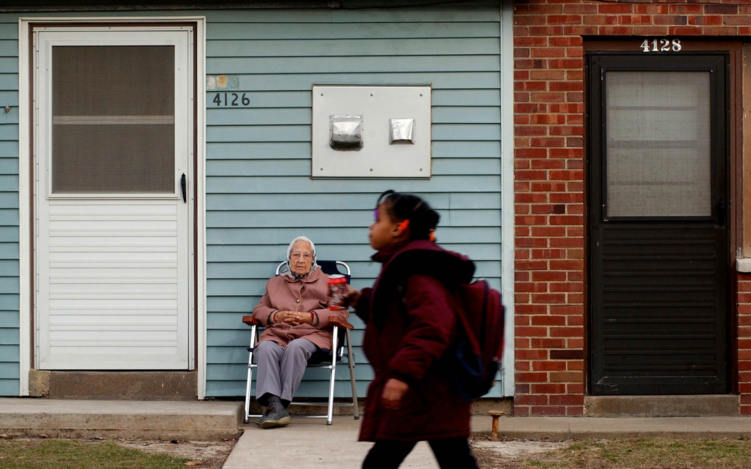 90-year-old Esther Funk of Moline watches the children come home from school Wednesday afternoon while she sitting outside her apartment in Springbrook Courts. Funk has lived in the public housing complex for 50-years. When the weather is nice she says she can usually be found outside enjoying the view from her front stoop. (Todd Mizener - Dispatch/Argus)