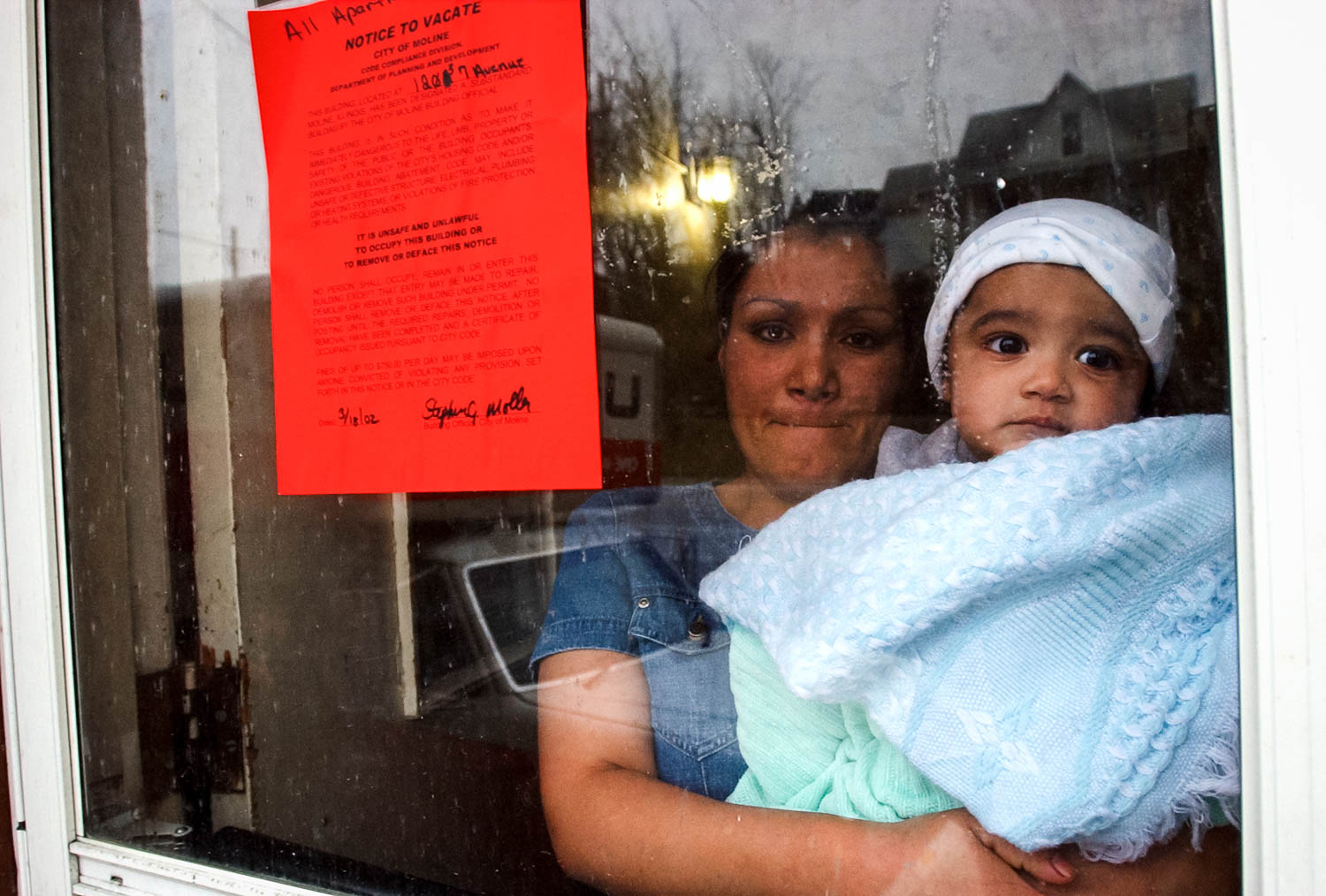 Luzmaria Carpia and her 7-month son Alejandero watch their friends and neighbors load their belongings into trucks and cars after the city of Moline evicted the apartment building's 10 families because safety violations. The families had less than one day of notice to move out. The mother of five children, whose husband is back in Mexico, didn't have any idea where she planned to go. (Todd Mizener - Dispatch/Argus)