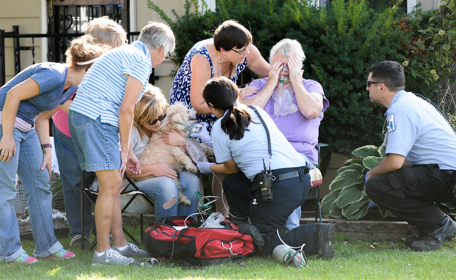 "Emergency personnel give oxygen to Pat Myers and her dog, while friends comfort her following a fatal fire at her home, 2413 44th Street Monday, Sept. 12, 2016, in Moline. Mrs. Myers husband, Howard ""Dave"" D. Myers, 80, died as a result of injuries suffered in the blaze, which broke out in the couple's basement. (Todd Mizener - Dispatch/Argus)"