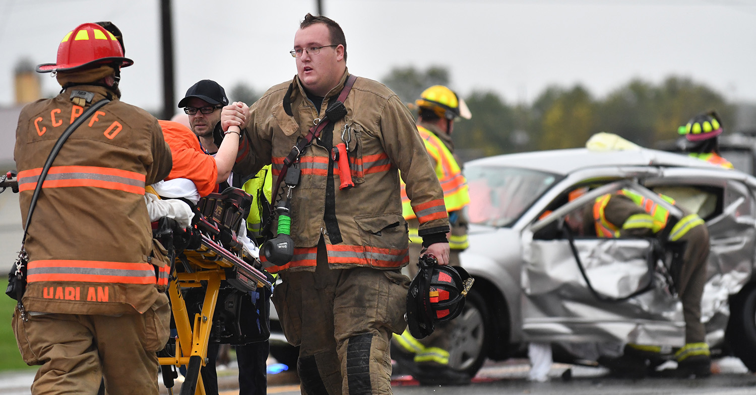 Lt. Austyn Wiesman, of the Carbon Cliff-Barstow Fire District, holds the hand of a driver involved in a three vehicle accident south of the intersection of Illinois 5 and Barstow Road Wednesday, Oct. 10, 2018, in Carbon Cliff, Ill.  (Todd Mizener - Dispatch/Argus)