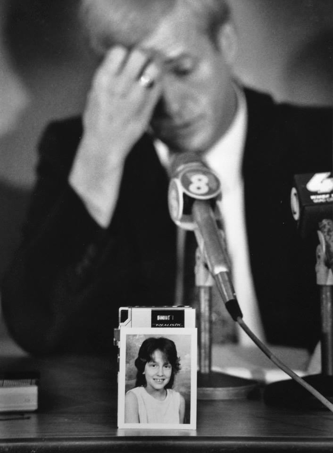 The school photo of murder victim Jennifer Ann Lewis rests against a reporter's tape recorder as Davenport investigator Don Schaeffer pauses to collect himself while discussing the details of the case. The smoldering body of the 9-year-old, from Rock Island, Illinois,  was found the night before near Jefferson Elementary School in Davenport, Iowa.
