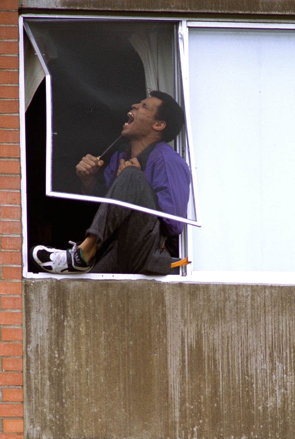 An unidentified man threatens to commit suicide in the window of his Moline apartment. Police were able to talk him out of the third story window without incident after an hour long stand-off. Police officials refuse to release the subject's name. (Todd Mizener - Dispatch/Argus)