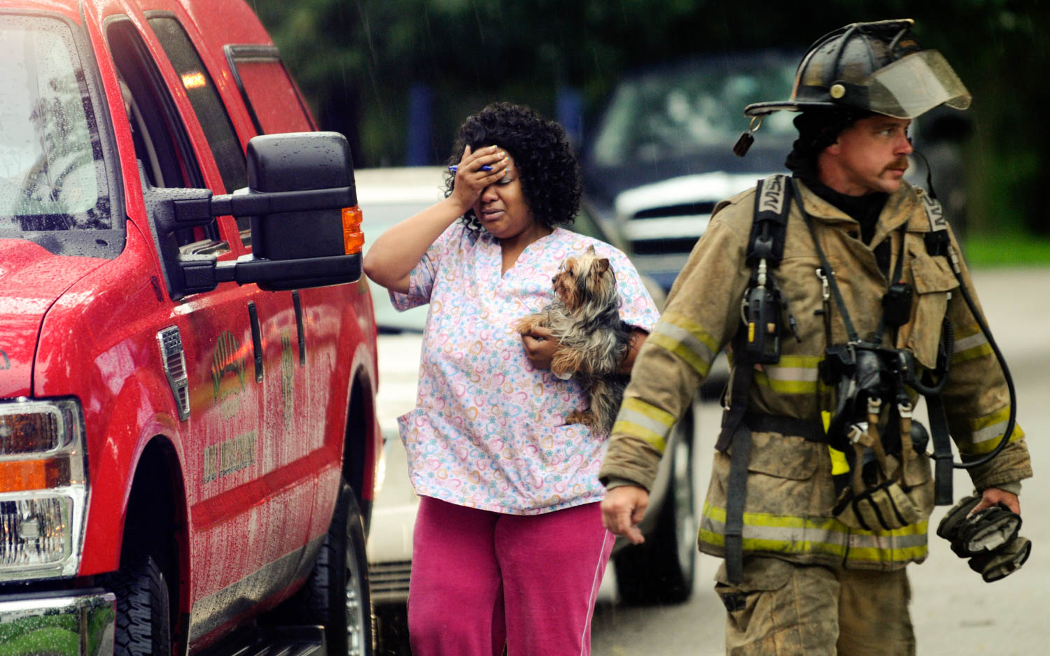 Katrina Jackson, of Moline, holds her dog close after the animal was rescued from a fire which damaged the duplex she lives at 1433 28th Ave. in Moline June 23, 2010. The fire was confined to a second floor bedroom on the south side of the duplex. (Todd Mizener - Dispatch/Argus)