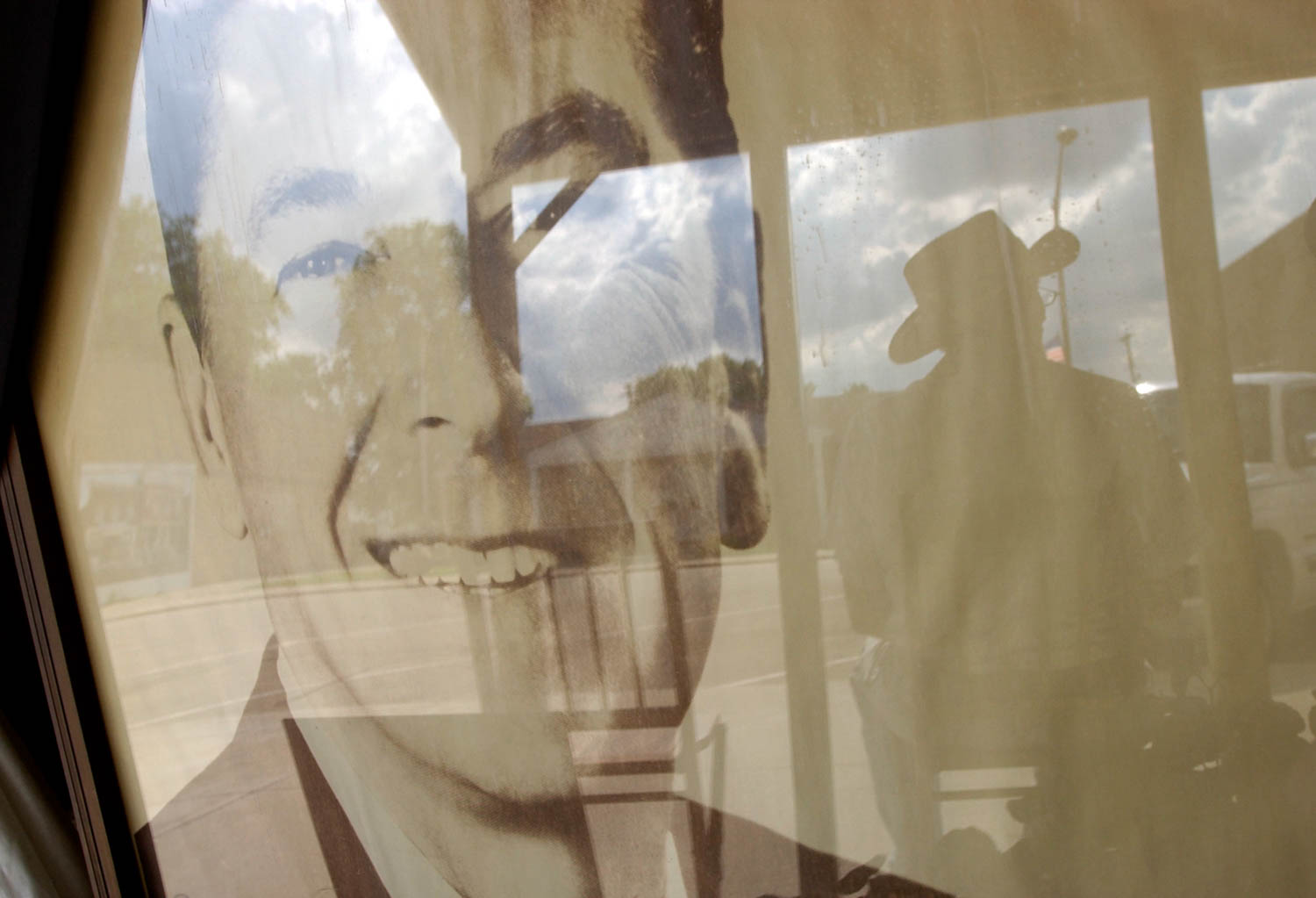 The reflection of Tim McLoughlin of Tampico Ill., casts a silhouette next to a large portrait of former President Ronald Reagan in the window of the Tampico historical society, Sunday afternoon. Reagan was born in Tampico, on Feb. 6, 1911 and died Saturday at the age of 93. (Todd Mizener - Dispatch/Argus)