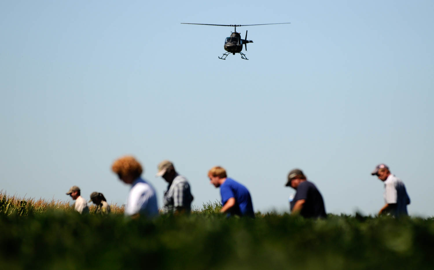 While helicopter searches from above volunteers and law enforcement search the soybean field north of the house where a 2-year-old boy went missing from on Monday August 6, 2012. The little boy was reported missing shortly after 10:30 a.m. this morning, he was found after being lost for hours in a farm field. According to Jeff Dale, chief deputy of the Mercer County Sheriff's Office, the boy was found uninjured three-quarters of a mile northwest of the home. (Todd Mizener - Dispatch/Argus)