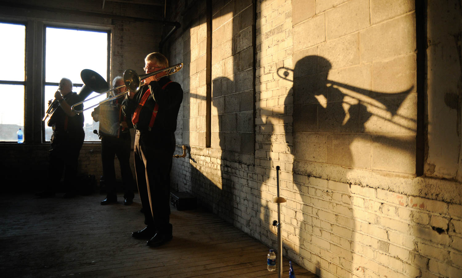 'Jinosterrifics' trombonist Jim Lee casts long shadow while he and his bandmates entertain the crowd at Thursday's ceremonial groundbreaking for the Jackson Square development late Wednesday afternoon in Rock Island. The Jackson Square project will redevelop the old Illinois Oil Products building, 321 24th Street, into 30 residential rental units and 3,700 square feet for future commercial space. (Todd Mizener - Dispatch/Argus)